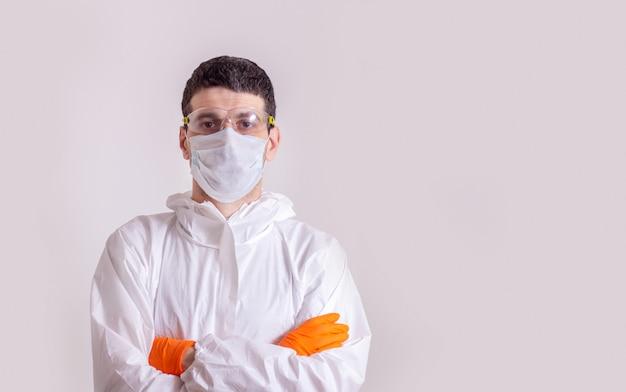 Maschile che indossa uno scudo facciale e una tuta dpi per l'epidemia di coronavirus o covid-19
