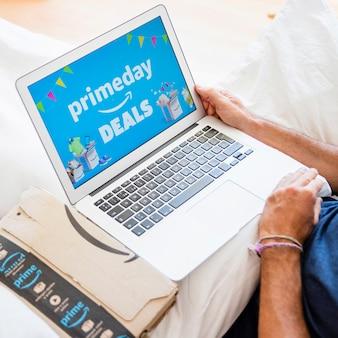 Maschio a letto con computer portatile e invio