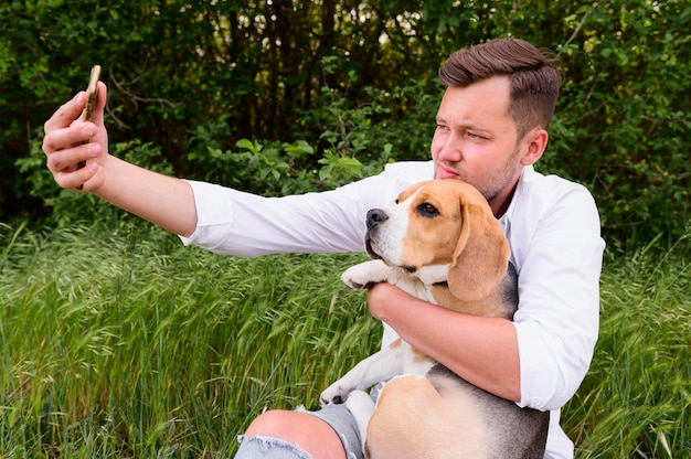 Maschio adulto che prende un selfie con il cane sveglio