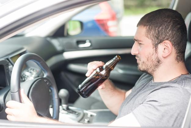 Maschio adulto con birra guida auto