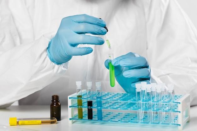 Maschio adulto del primo piano che preleva i campioni medici