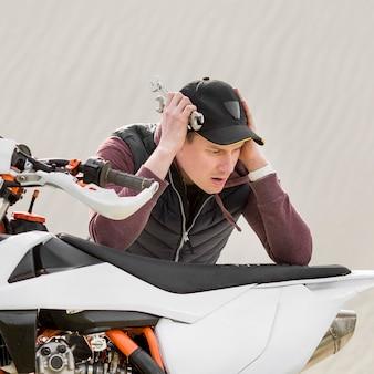 Maschio adulto del primo piano che prova a riparare motocicletta