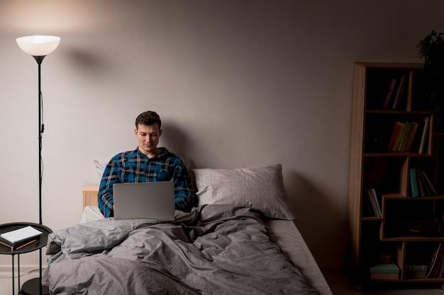 Maschio adulto di vista frontale che lavora dal letto