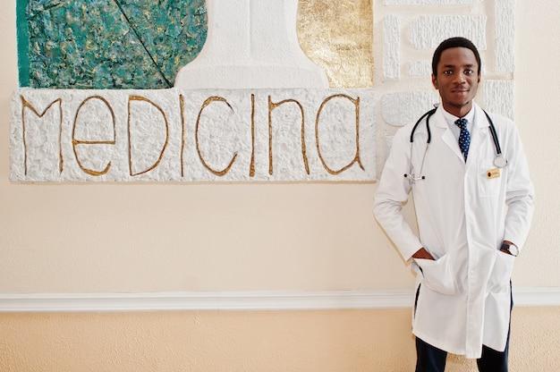 Maschio afroamericano dello studente di medico al cappotto del laboratorio con lo stetoscopio dentro l'università medica.