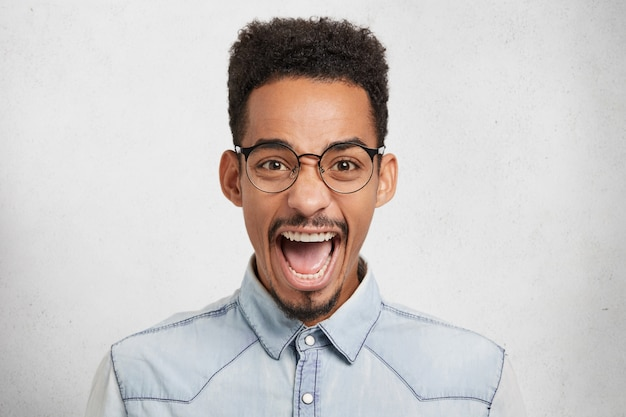 Maschio afroamericano emotivo con occhiali rotondi, apre la bocca per l'eccitazione, esclama con gioia
