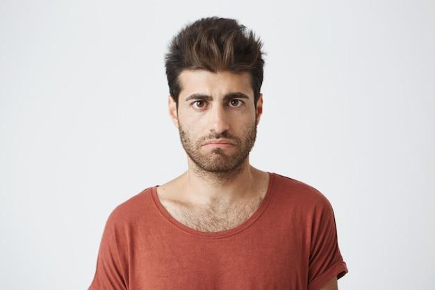 Maschio alla moda barbuto che ha dispiaciuto sembrare che sta in panno casuale contro la parete bianca. giovane che ha alcuni problemi a guardare con insoddisfazione e malcontento