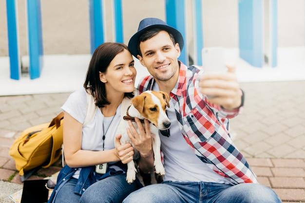 Maschio alla moda che indossa cappello e camicia a scacchi, facendo selfie con la sua ragazza che tiene in mano un cane, avendo espressioni felici. giovane maschio e femmina che hanno rilassamento insieme sulle vacanze estive