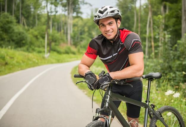 Maschio allegro del ciclista che si appoggia la sua bici sul sentiero forestale