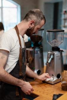 Maschio alto angolo che produce caffè