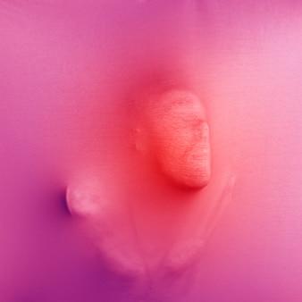 Maschio anonimo che preme un panno rosa
