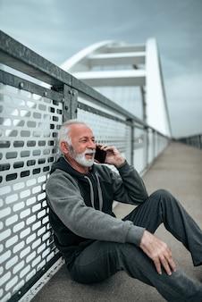 Maschio anziano attivo prendendo una pausa e parlando al telefono.