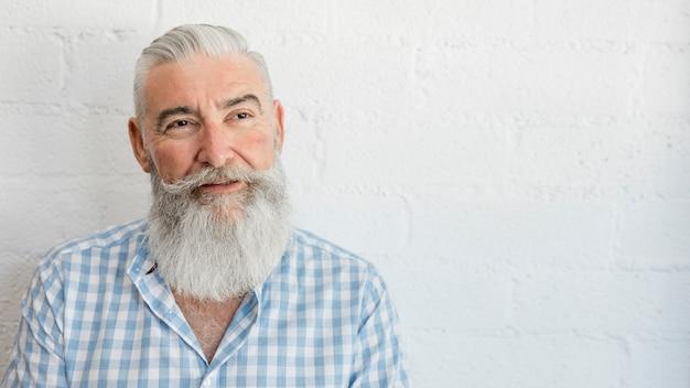 Maschio anziano barbuto bello in camicia in studio