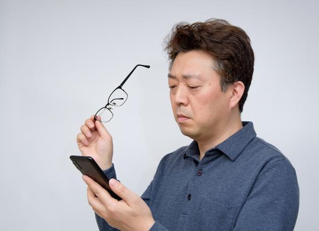 Maschio asiatico che prova a leggere qualcosa sul suo telefono cellulare. vista scarsa, presbiopia, miopia.