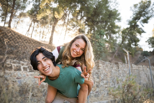 Maschio asiatico con la ragazza sulla parte posteriore che si diverte insieme