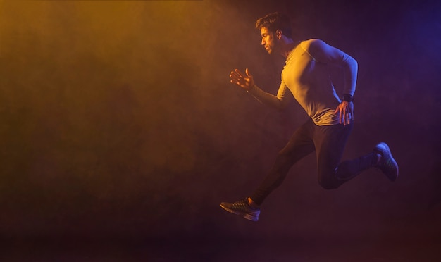 Maschio atletico che salta nello studio scuro