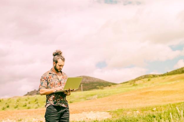 Maschio barbuto che lavora al computer portatile in campagna