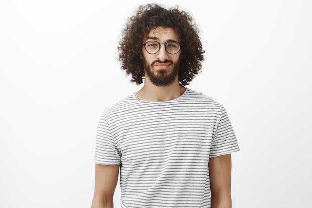 Maschio barbuto di bell'aspetto insicuro con i capelli ricci in occhiali neri alla moda, che solleva le sopracciglia e guarda con dubbio