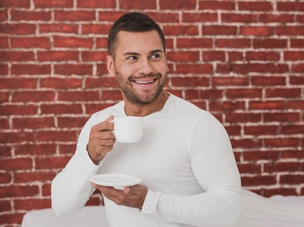 Maschio bello che mangia una tazza di caffè
