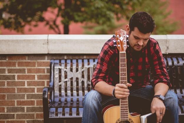 Maschio bianco attraente che si siede su una panchina che tiene la chitarra