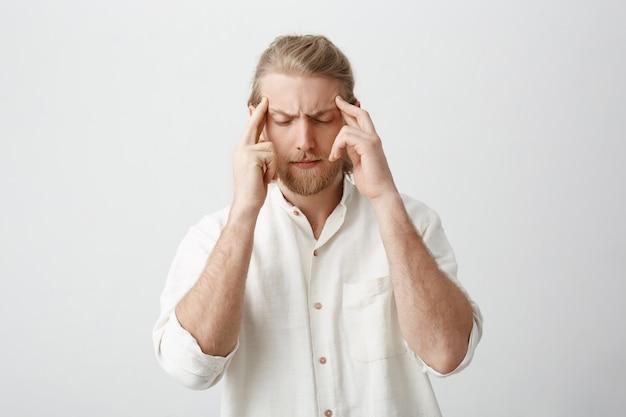 Maschio biondo bello determinato stanco con barba e baffi, tenendo le dita sulle tempie, accigliato, sentendo dolore o cercando di concentrarsi
