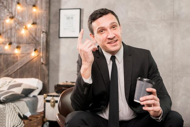 Maschio carismatico che pondera tenendo la tazza di caffè in mano