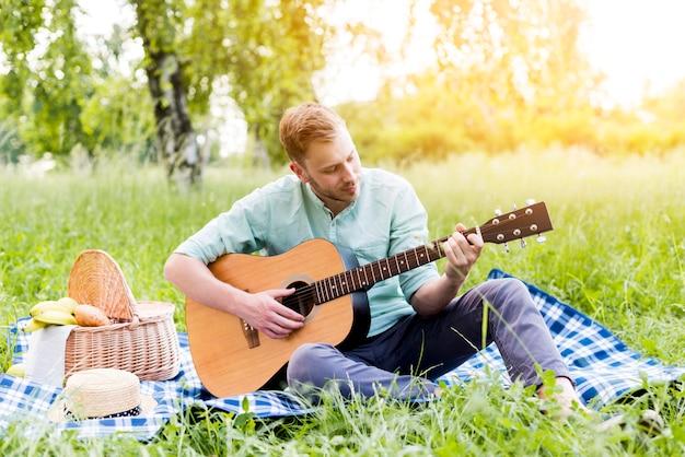 Maschio che gioca chitarra sul picnic in estate