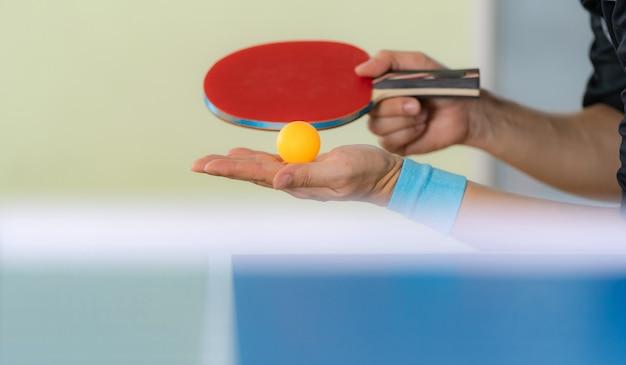 Maschio che gioca ping-pong con la racchetta e la palla in una palestra