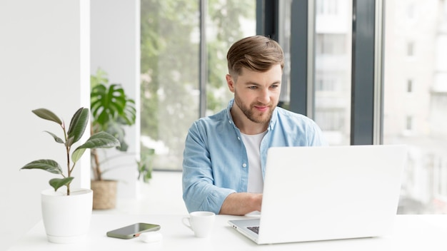 Maschio che lavora al computer portatile