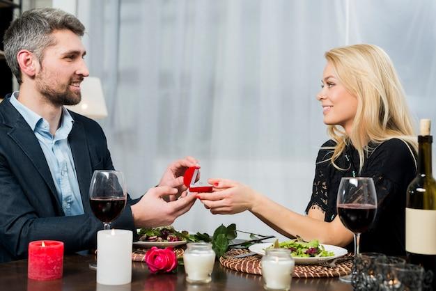 Maschio che presenta scatola regalo con anello per femmina bionda al tavolo con piatti e fioritura