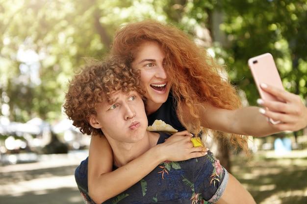 Maschio che tiene sulla schiena la sua ragazza mentre guarda lo smartphone