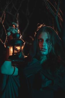 Maschio che tiene una lanterna nella notte