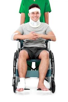 Maschio con braccio rotto e piede con sedia a rotelle