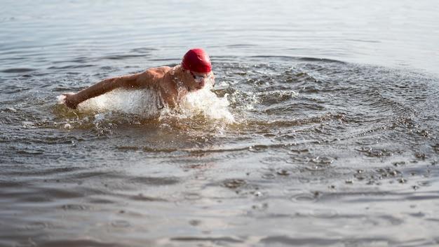 Maschio con cappuccio rosso nuotare nel lago