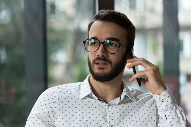 Maschio con gli occhiali parlando al telefono
