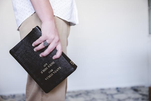 Maschio con in mano la bibbia