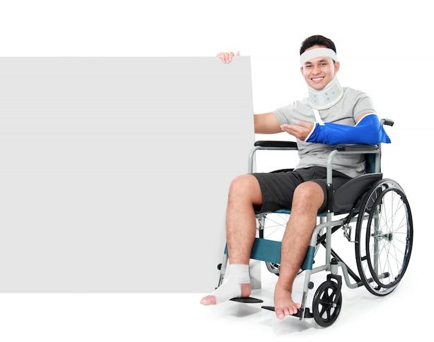 Maschio con la gamba rotta che si siede sulla sedia a rotelle e che presenta al bordo in bianco