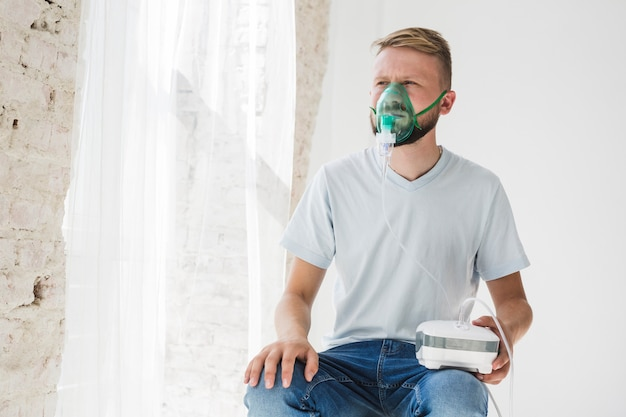 Maschio con nebulizzatore d'asma