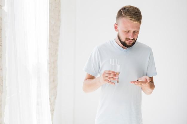 Maschio con pillole in mano