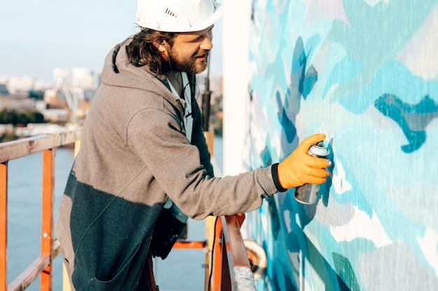 Maschio costruttore pittore professionista dipinge il muro di un nuovo edificio