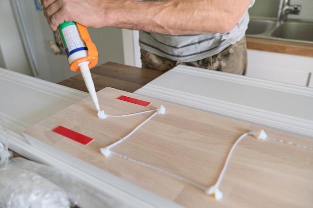 Maschio del carpentiere che usando la colla per costruzioni