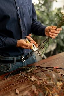 Maschio del fiorista che taglia i gambi del fiore