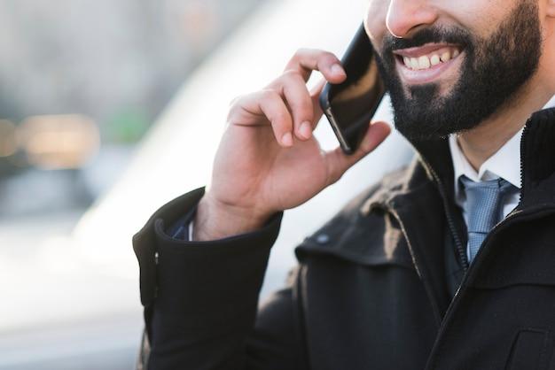 Maschio del primo piano che parla sopra il telefono