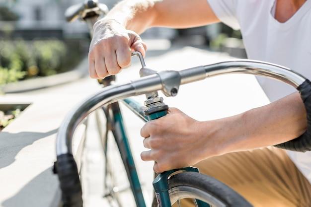 Maschio del primo piano che ripara la sua bici
