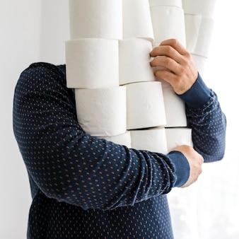 Maschio del primo piano con la pila di carta igienica