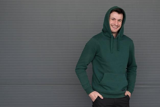 Maschio del ritratto che indossa maglia con cappuccio verde
