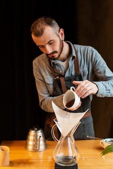 Maschio dell'angolo alto che prepara caffè