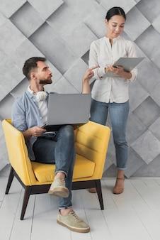 Maschio dell'angolo alto sulla sedia che parla con il collega