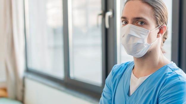Maschio dell'infermiera di vista laterale con la mascherina medica
