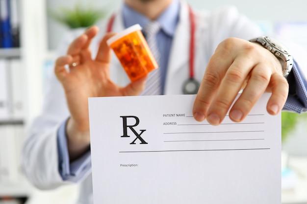 Maschio di medicina medico tenere in mano un barattolo di pillole e dare prescrizione al paziente