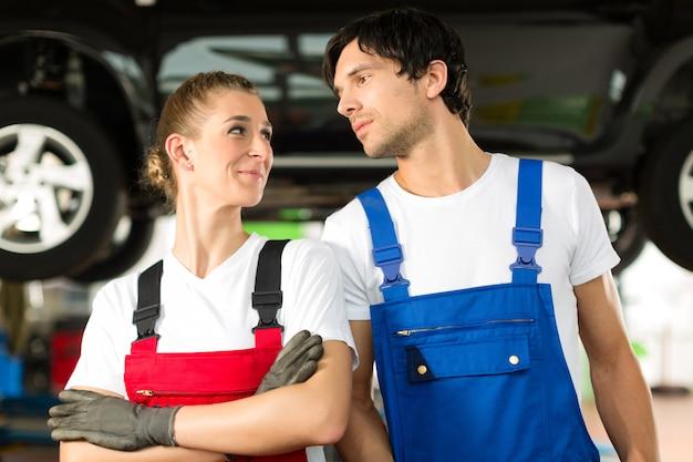 Maschio e femmina dei meccanici di automobile davanti all'automobile